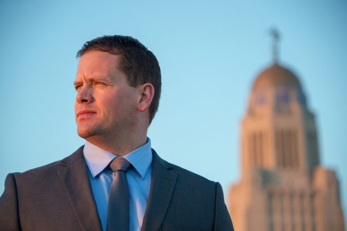 Photo: A business man stands near the Nebraska State Capitol.