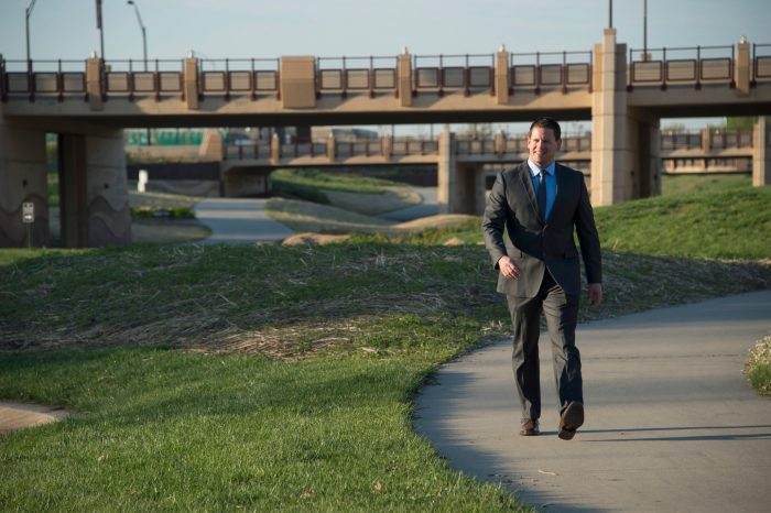 Photo: A business man walks along the sidewalk near a bridge.