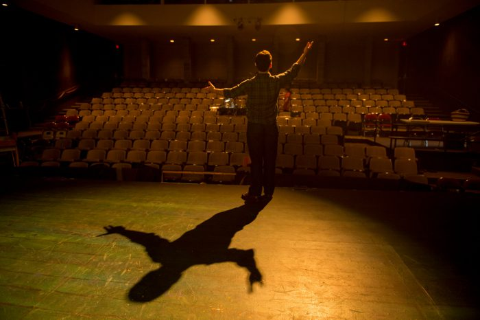 Photo: A young man stands on the stage at the Lincoln Community Playhouse during a lighting test.