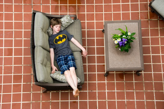 Photo: An elementary age boy relaxes on the patio.
