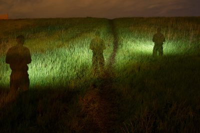 Photo: Multiple exposure of a man illuminating a field with a flashlight.
