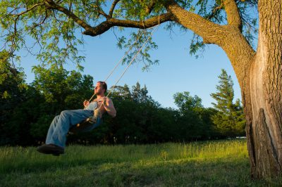 Photo: A man swings on a tree swing.