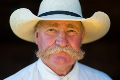 Photo: A portrait of a rancher wearing a cowboy hat.