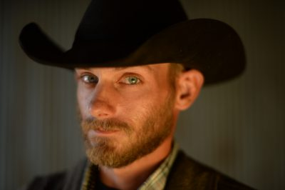 Photo: A portrait of a young man wearing a cowboy hat.