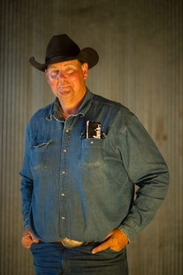 Photo: A portrait of a rancher wearing a cowboy hat.