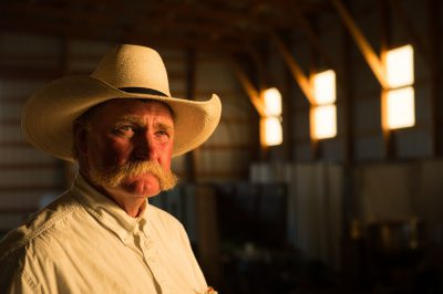 Photo: A portrait of a rancher wearing a cowboy hat in a barn.
