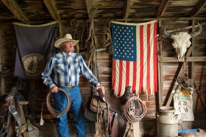 Photo: A still life with an American flag and a rancher in his barn.