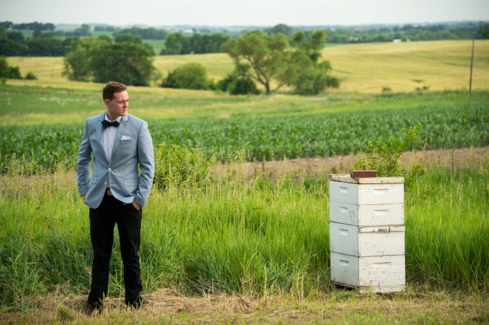 Photo: A young man in a suit stands near a beehive in a field.