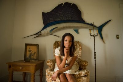 Photo: A teenage girl sits in a chair below a decorative fish.
