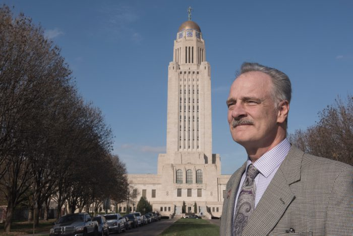 Photo: A man stands in front of the capitol building in Lincoln, Nebraska.