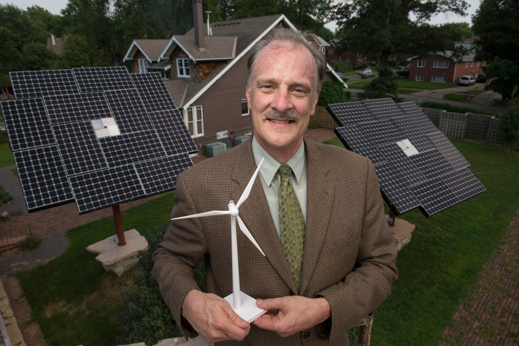 Photo: A man with a model windmill and solar panels at his home.