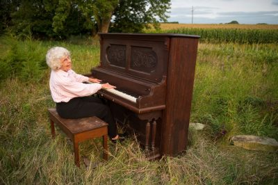 Photo: A woman sings and plays a piano in a field in Nebraska.