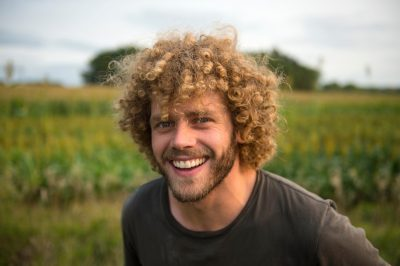 Photo: A man with curly hair on a farm in Nebraska.
