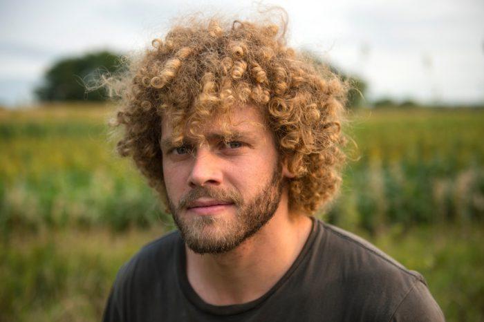 Photo: A man with curly hair on a farm in Nebraska.