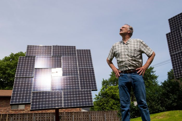 Photo: A man stands near his solar panels.