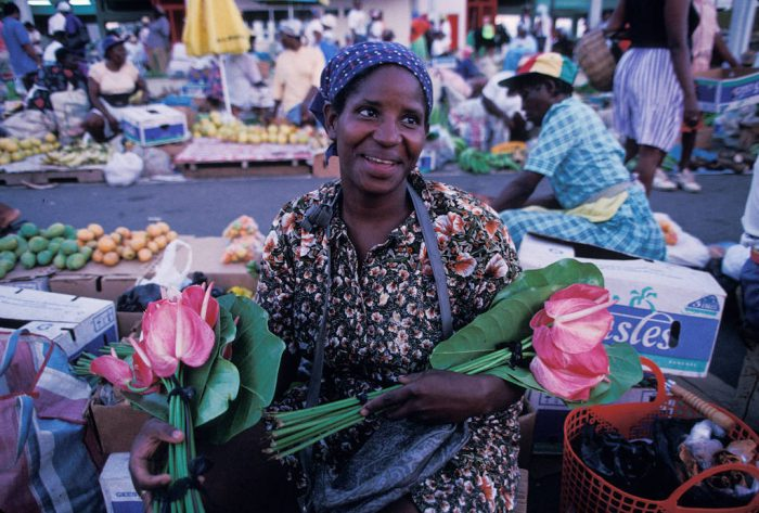 Photo: A woman sells flowers at a local market in St. Lucia in the Caribbean.