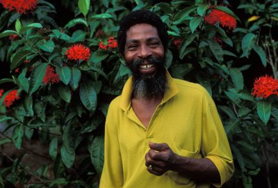 Photo: A man from St. Lucia in the Caribbean poses in front of vibrant red flowers.
