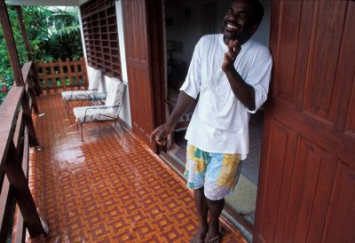 Photo: A man from St. Lucia in the Caribbean poses leisurely outside his home.