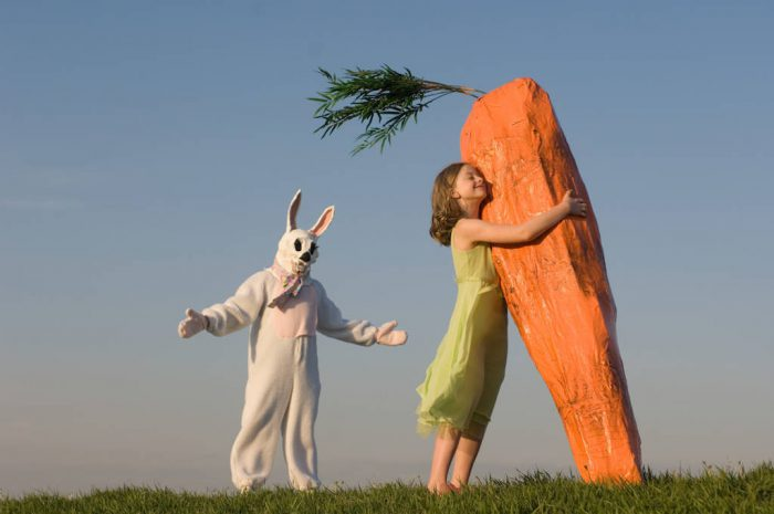 Photo: A little girl hugs a giant carrot that belongs to the Easter Bunny.