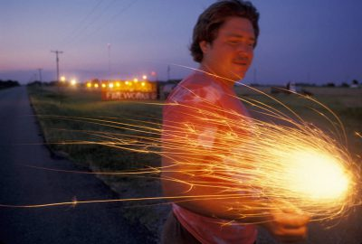 Photo: A man holds a firework near a stand in Oklahoma.