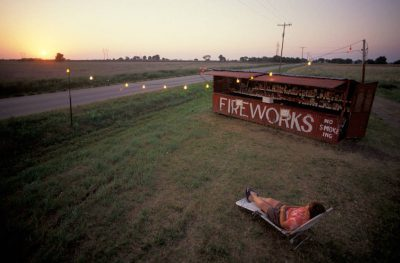 Photo: A woman relaxes on a lawnchair outside a fireworks stand inOklahoma.