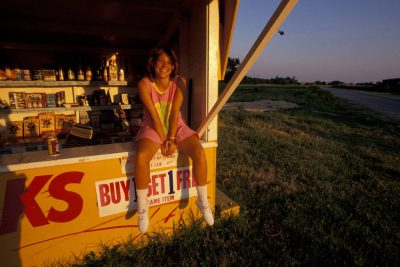 Photo: A woman smiles as she sits on the counter of a fireworks stand in Oklahoma.