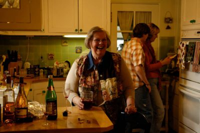 Photo: A woman laughs while drinking fruit juice after a Thanksgiving meal.