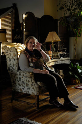 Photo: An older woman sits in an armchair during Thanksgiving.
