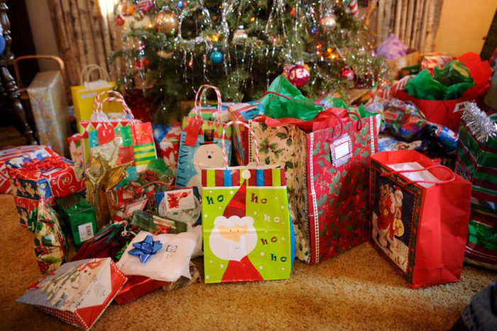 Photo: Christmas presents sit under a Christmas tree, ready to be opened.