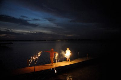 Photo: Two girls play with sparklers at dusk on a dock in Leech Lake near Walker, MN.