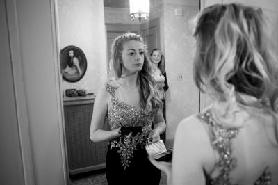 Photo: A teenage girl checks her reflection in the mirror before her senior prom.