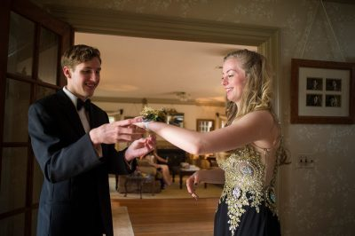 Photo: A teenage boy places a corsage on his date's hand before they go to the prom.