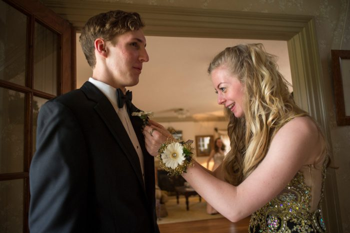 Photo: A teenage girl pins a corsage on her date's jacket before they go to the prom.