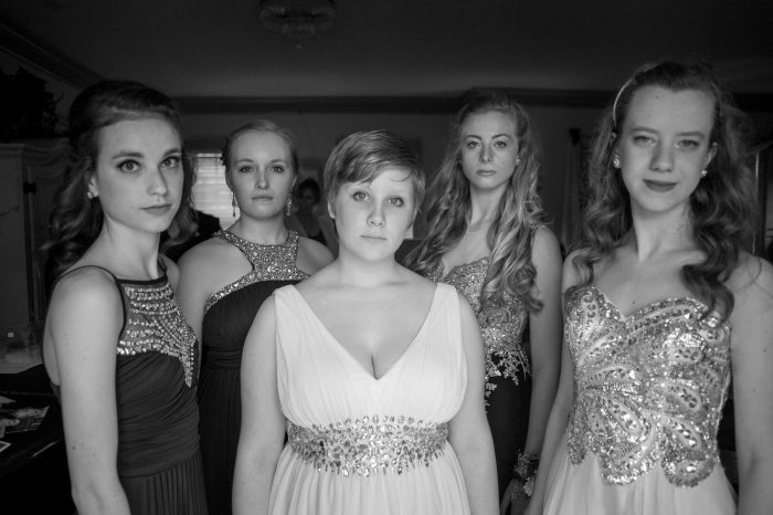 Photo: Teenage girls getting their pictures taken before heading to their senior prom.