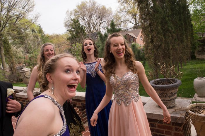 Photo: Teenage girls laughing while getting their pictures taken before heading to their senior prom.