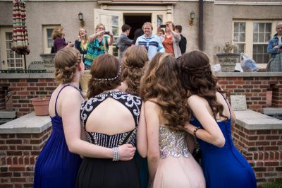 Photo: Teenage girls pose for portraits taken by their parents before heading to their senior prom.