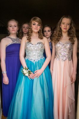 Photo: Teenage girls pose for portraits before heading to their senior prom.