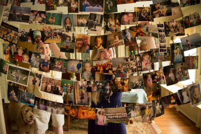 Photo: A teenage girl and her mother stand behind a display of childhood photos at her high school graduation party.