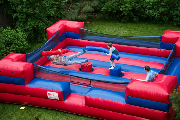 Photo: An elementary age boy knocks over his opponent in an inflatable jousting ring.