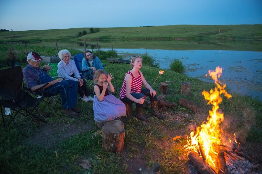 Photo: A family sits around a campfire at a fishing night at the Valparaiso pond in Valparaiso, Nebraska.
