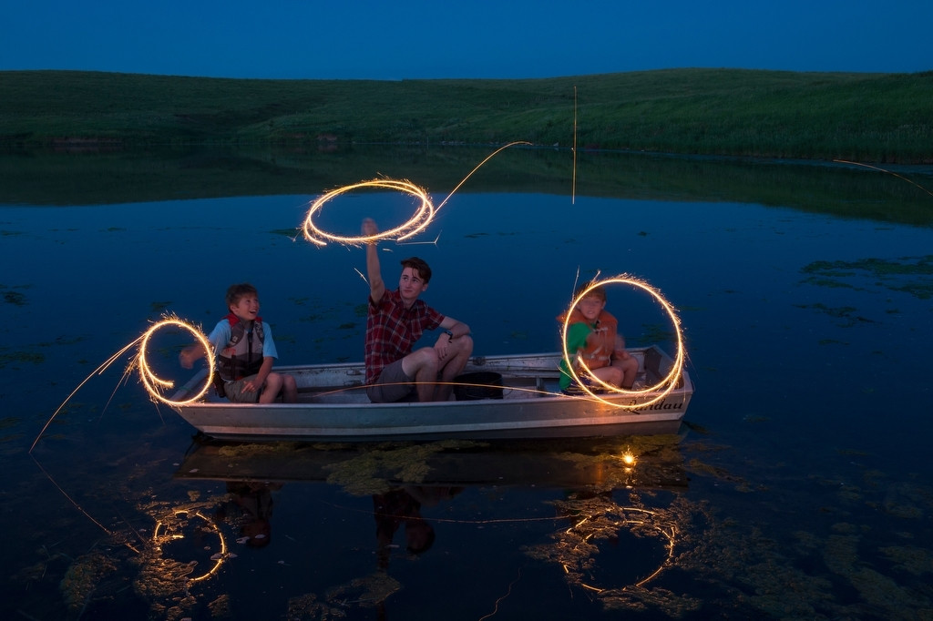 Photo: Three boys play with sparklers on a boat at the Valparaiso pond.