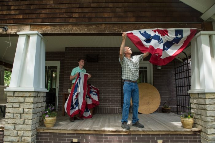 Photo: Two men hang up patriotic banners.