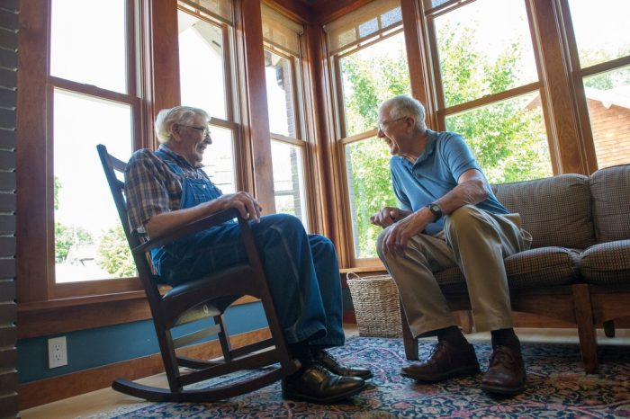 Photo: Two men have a conversation in a sun filled home.