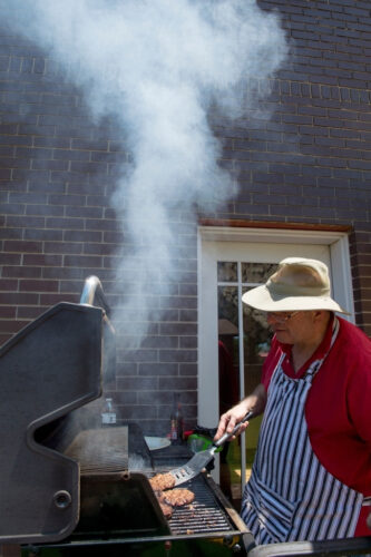 Photo: A man flips burgers on a grill at a backyard bar-b-que.