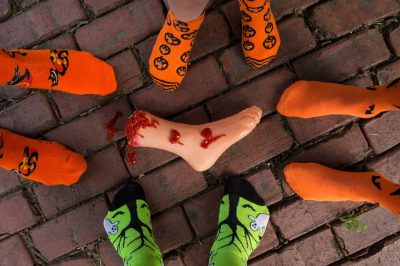 Photo: A fake bloody foot surrounded by Halloween clad feet.