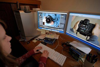 Photo: A woman works on images using a Mac system at Joel Sartore Photography.