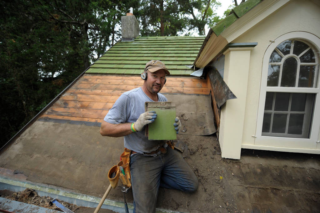 Photo: A man works on a tile garage roof.