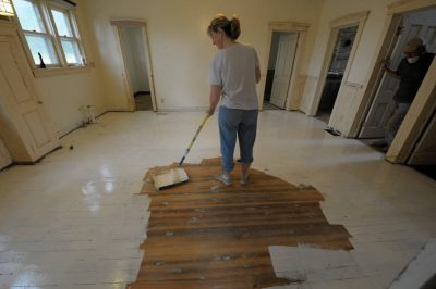 Photo: A woman paints the Dunbar farmhouse floor.