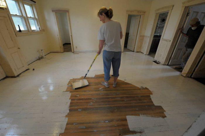 Photo: A woman paints the Dunbar farmhouse floor.