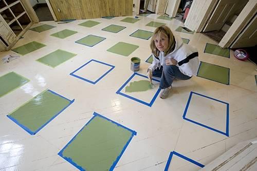 Photo: A woman paints a pattern on the kitchen floor of a farmhouse near Dunbar, Nebraska.